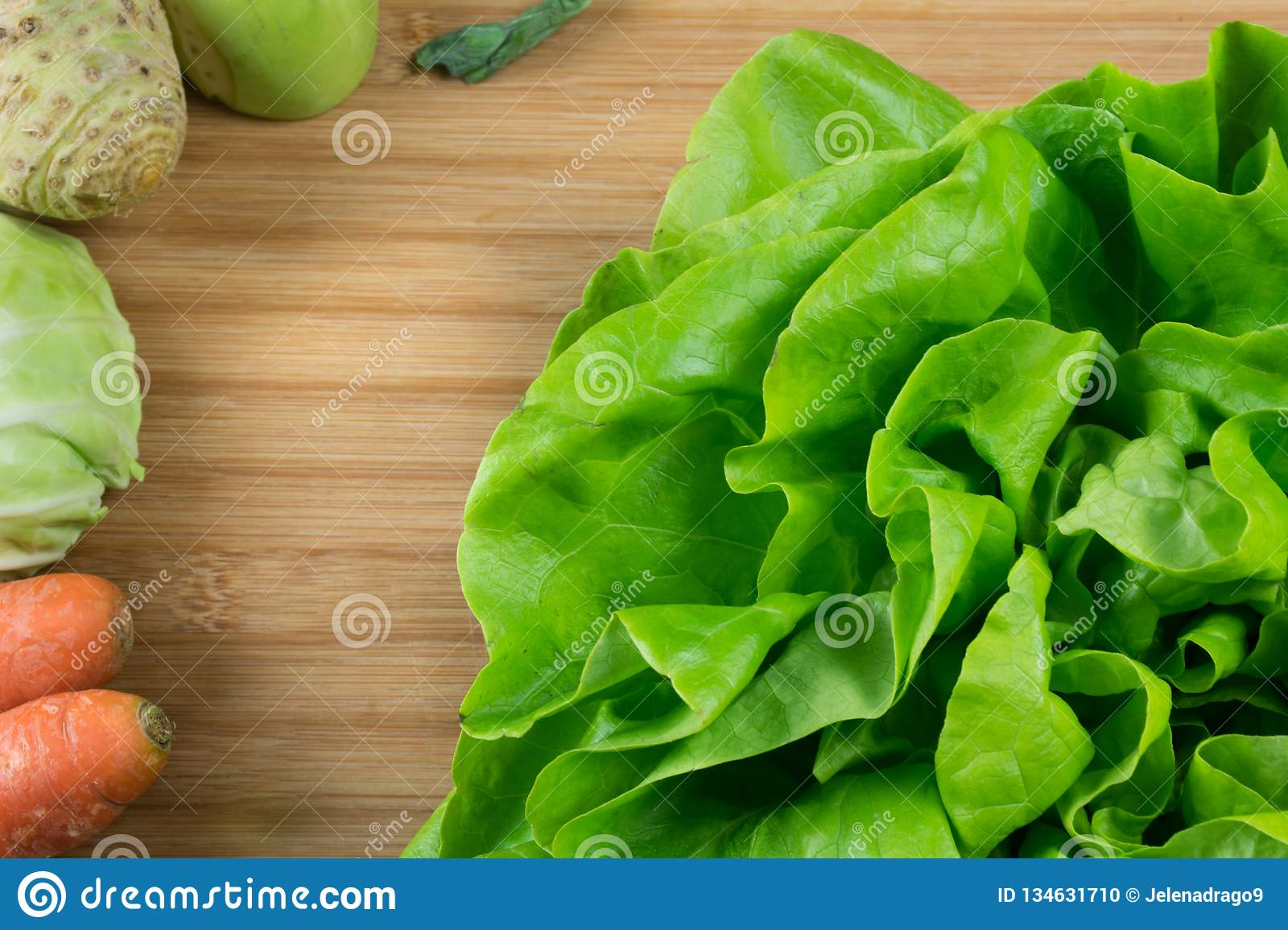 Fresh green lettuce on the cod board and fresh vegetables, carrot, cabbage, celery and kohlrabi on the side.