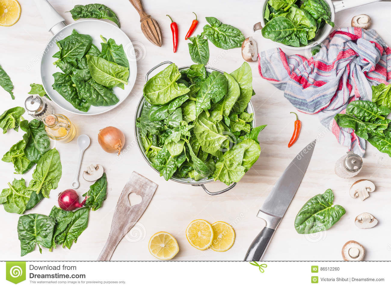 fresh green spinach leaves colander white kitchen table background cooking ingredients spoon knife top view 86512260