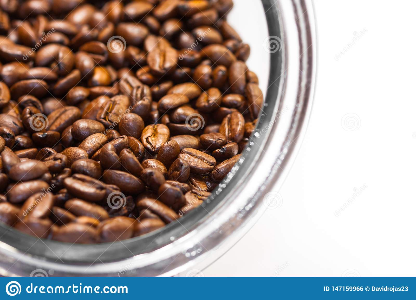 Fresh and ground roasted coffee beans from the coffee plant inside a cylindrical glass jar