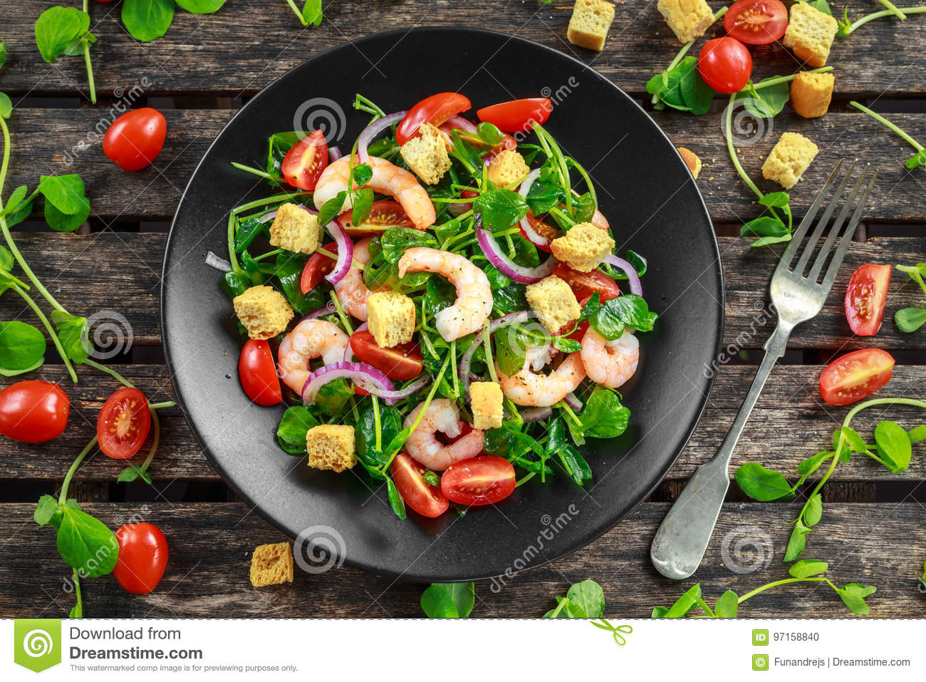 Fresh Healthy Prawns salad with tomatoes, red onion on black plate. concept healthy food