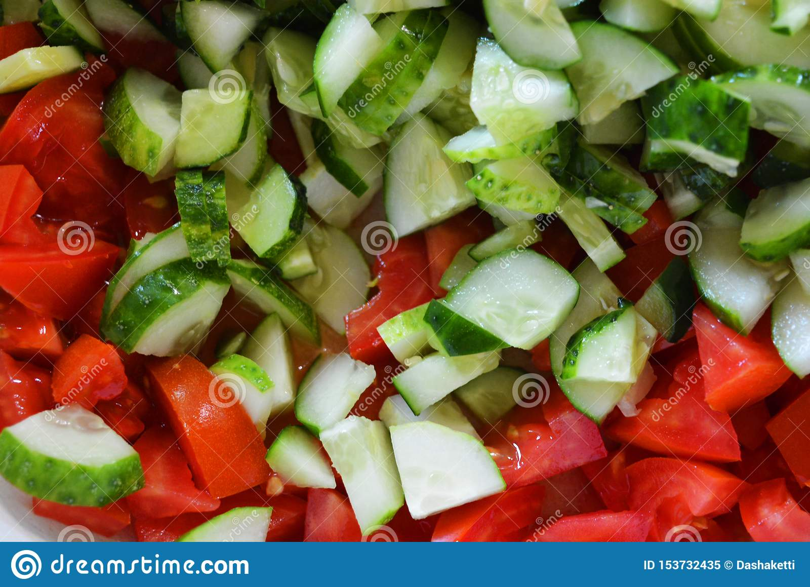 Fresh healthy vegetables, small slices of green cucumbers and red tomatoes for summer salad, ingredients for salad.