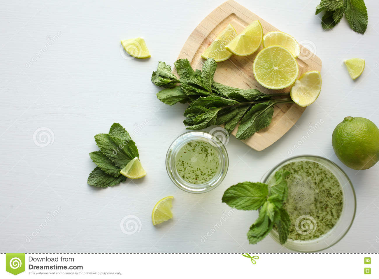 Fresh home-made lemonade with lemon, lime and mint in a glass on white background and ingredients laying on the table