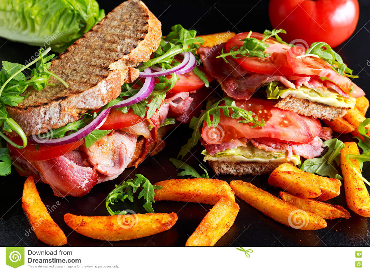 Fresh homemade BLT sandwich on grilled bread with bacon, lettuce, beef tomato, red onions, wild rocket and chips