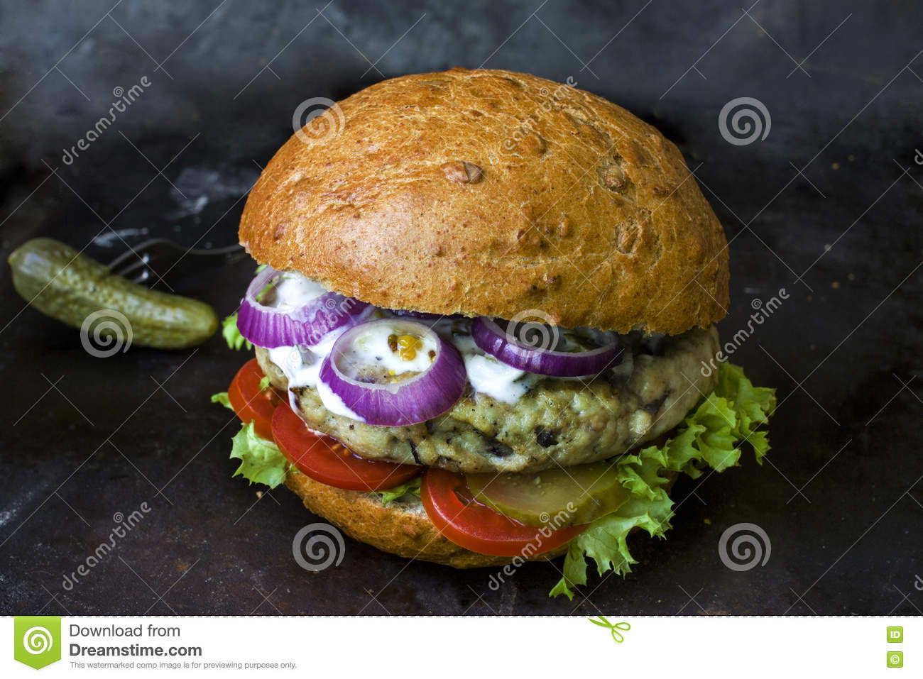 Fresh homemade burger with spicy sauce,cornichons and herbs over dark metal background