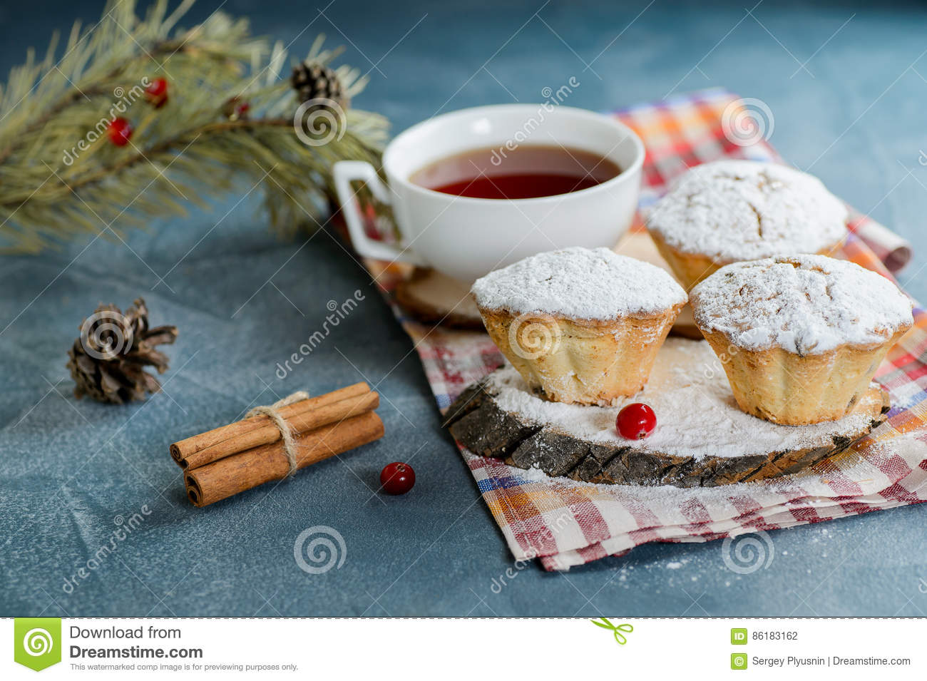 Fresh homemade cranberry muffins in icing sugar with fir-tree branches and tea.