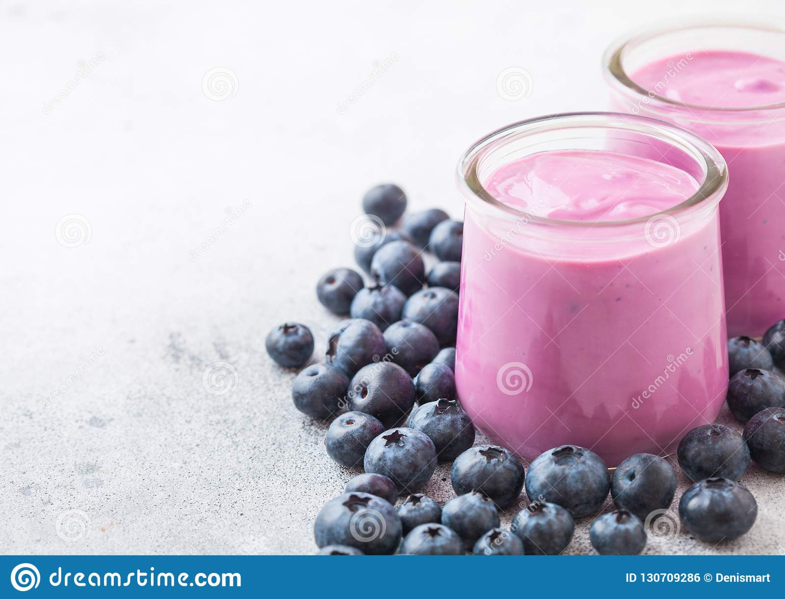 Fresh hommemade creamy blueberry yoghurt with fresh blueberries on stone kitchen table background