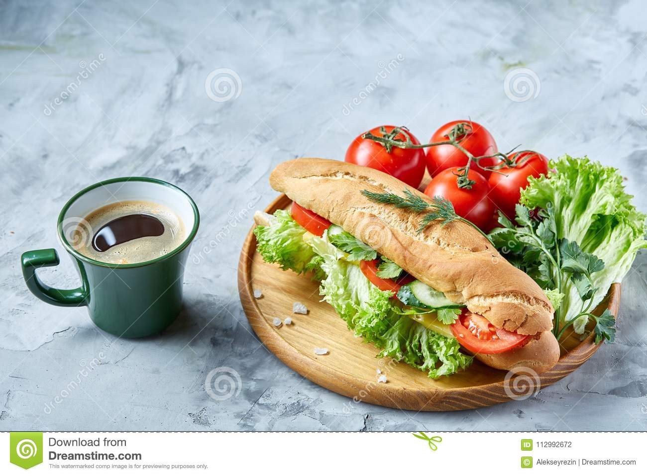 Fresh sandwich with lettuce, tomatoes, cheese on wooden plate, cup of coffee on white background, selective focus