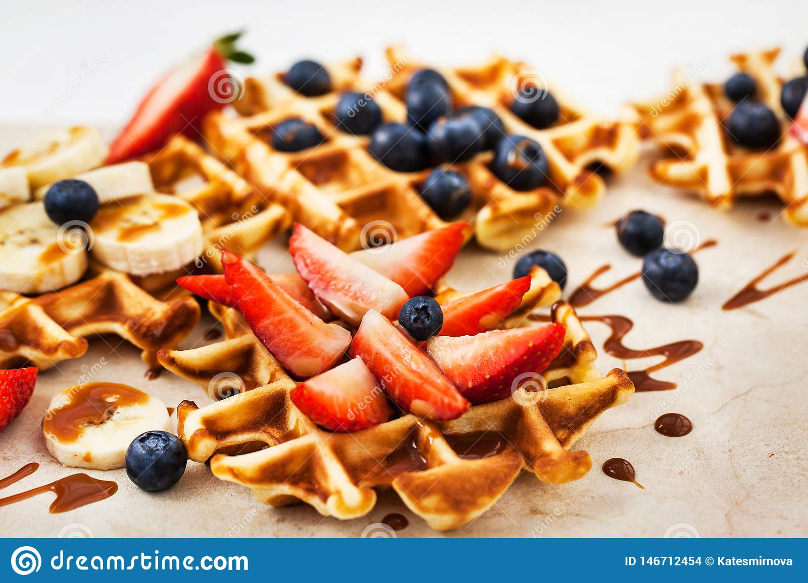 Fresh homemade waffles decorated with blueberries, strawberries and bananas