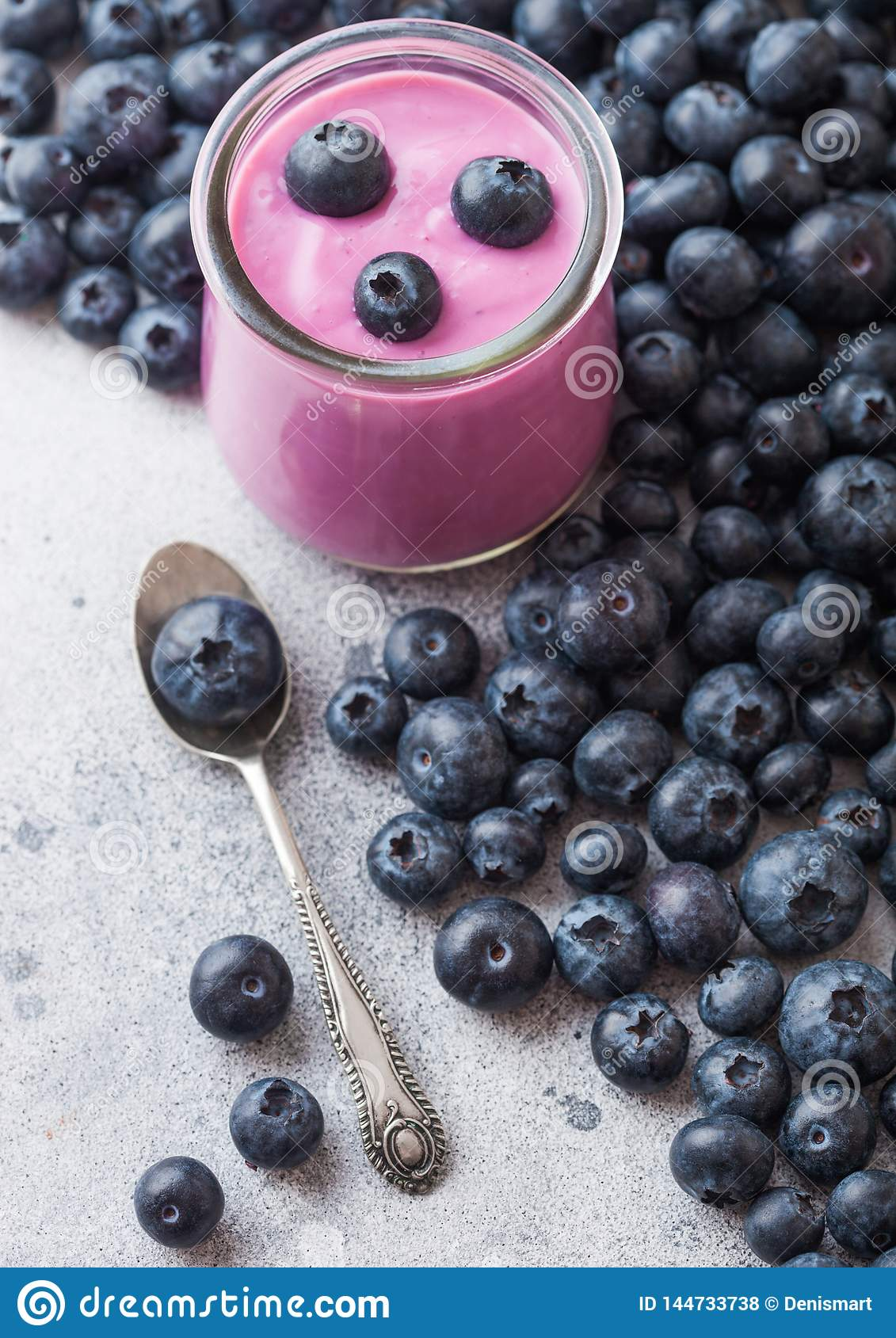 Fresh hommemade creamy blueberry yoghurt with fresh blueberries and silver spoon on stone kitchen table background