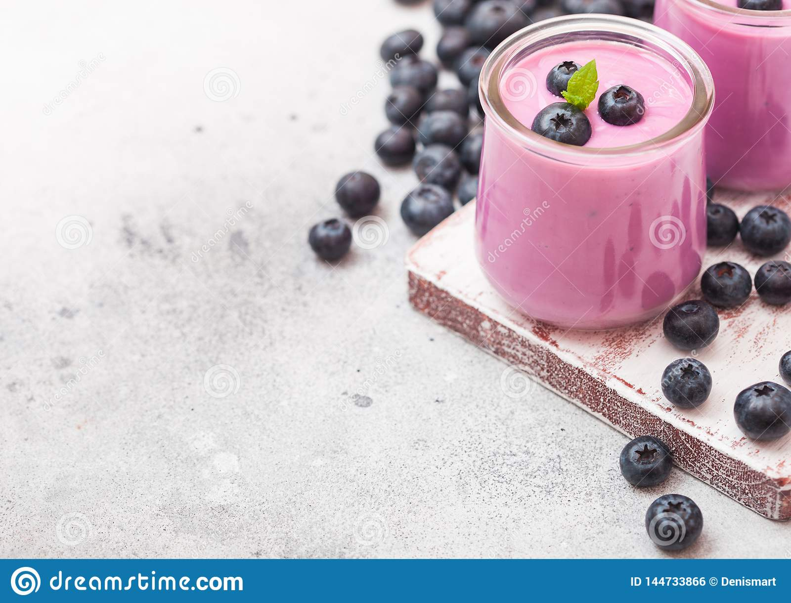 Fresh hommemade creamy blueberry yoghurt with fresh blueberries on vintage wooden board on stone kitchen table background