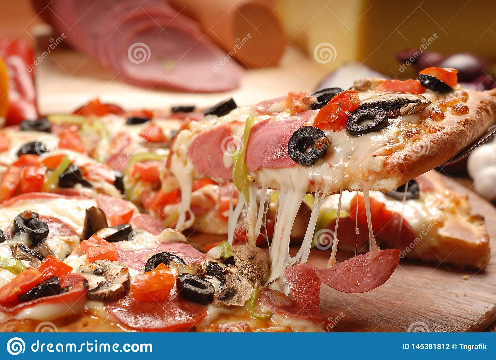 Hot pizza slice with melting cheese on a rustic wooden table