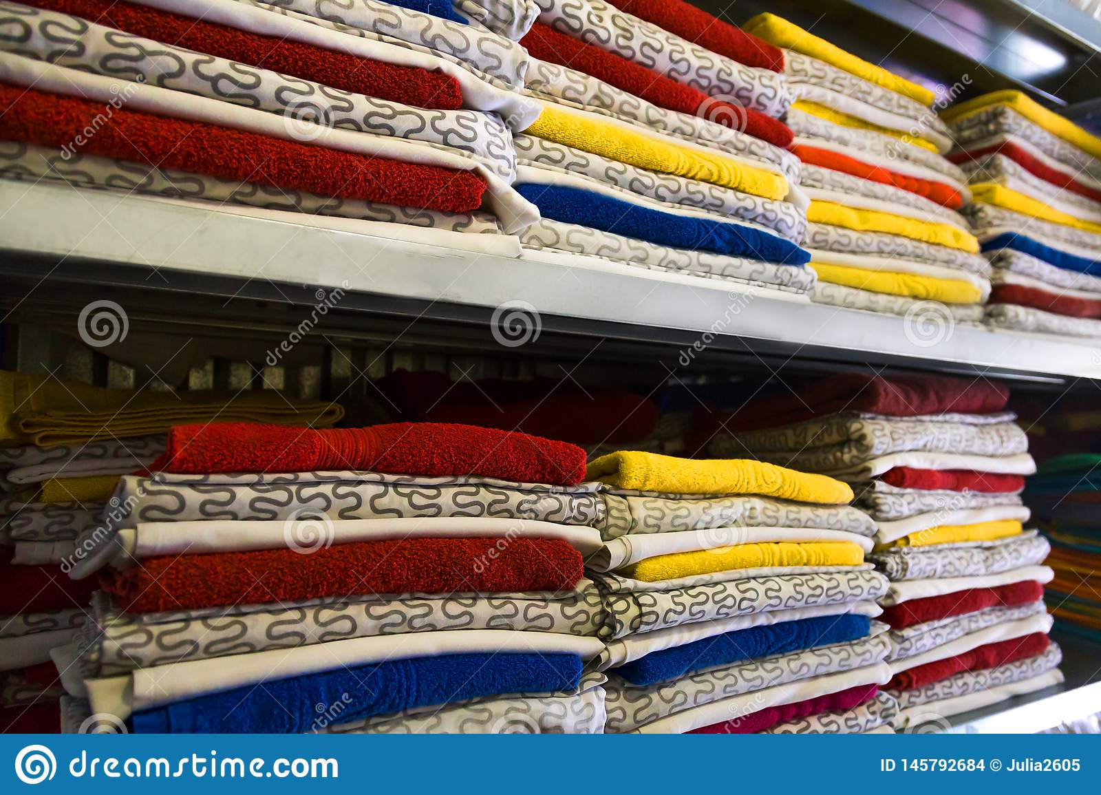 Fresh hotel towels and bed linen are stacked on the shelf