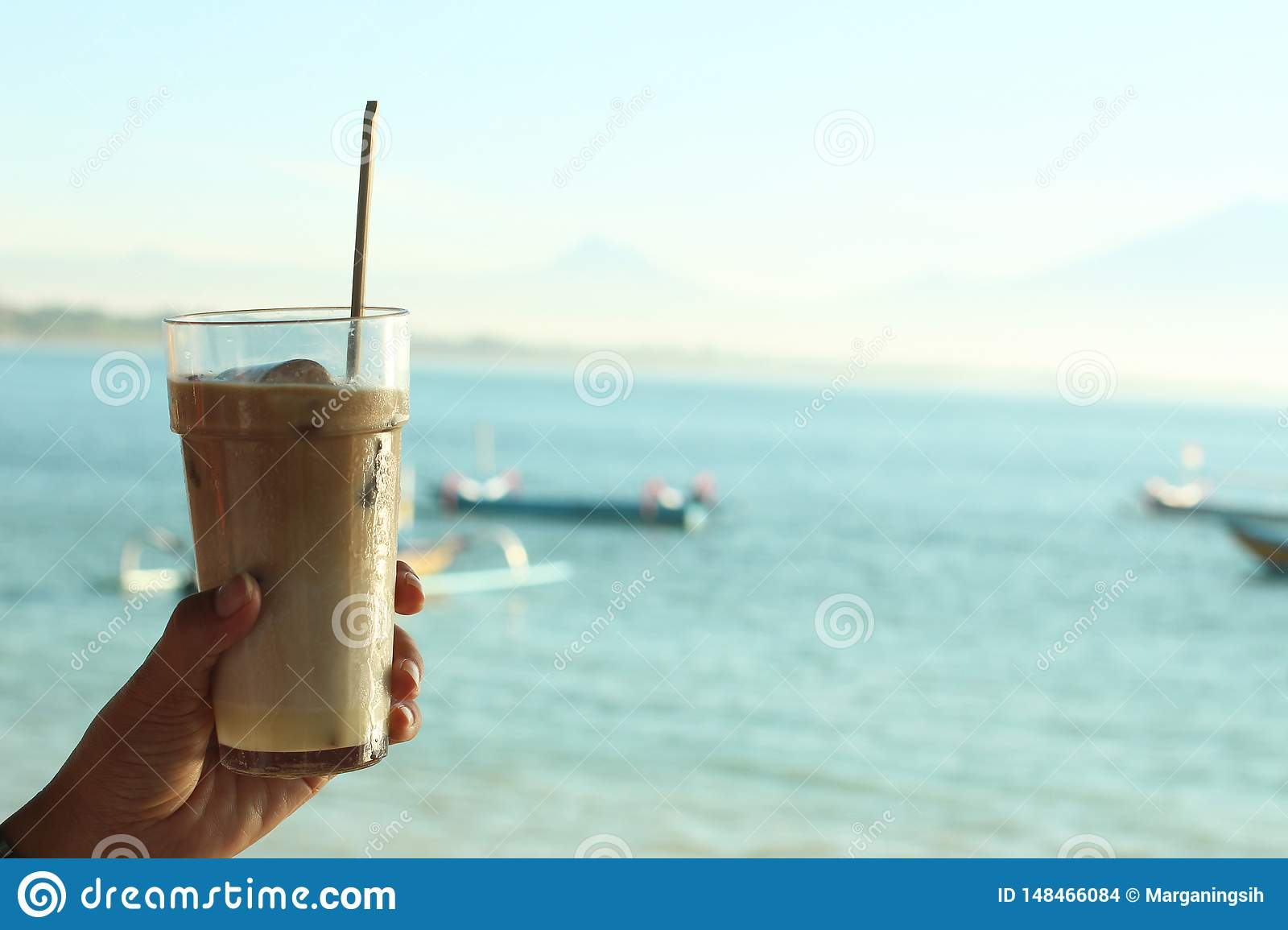 Fresh Ice Coffee Milk with blue beach background at day time. Holiday mood. Fresh drink in hand