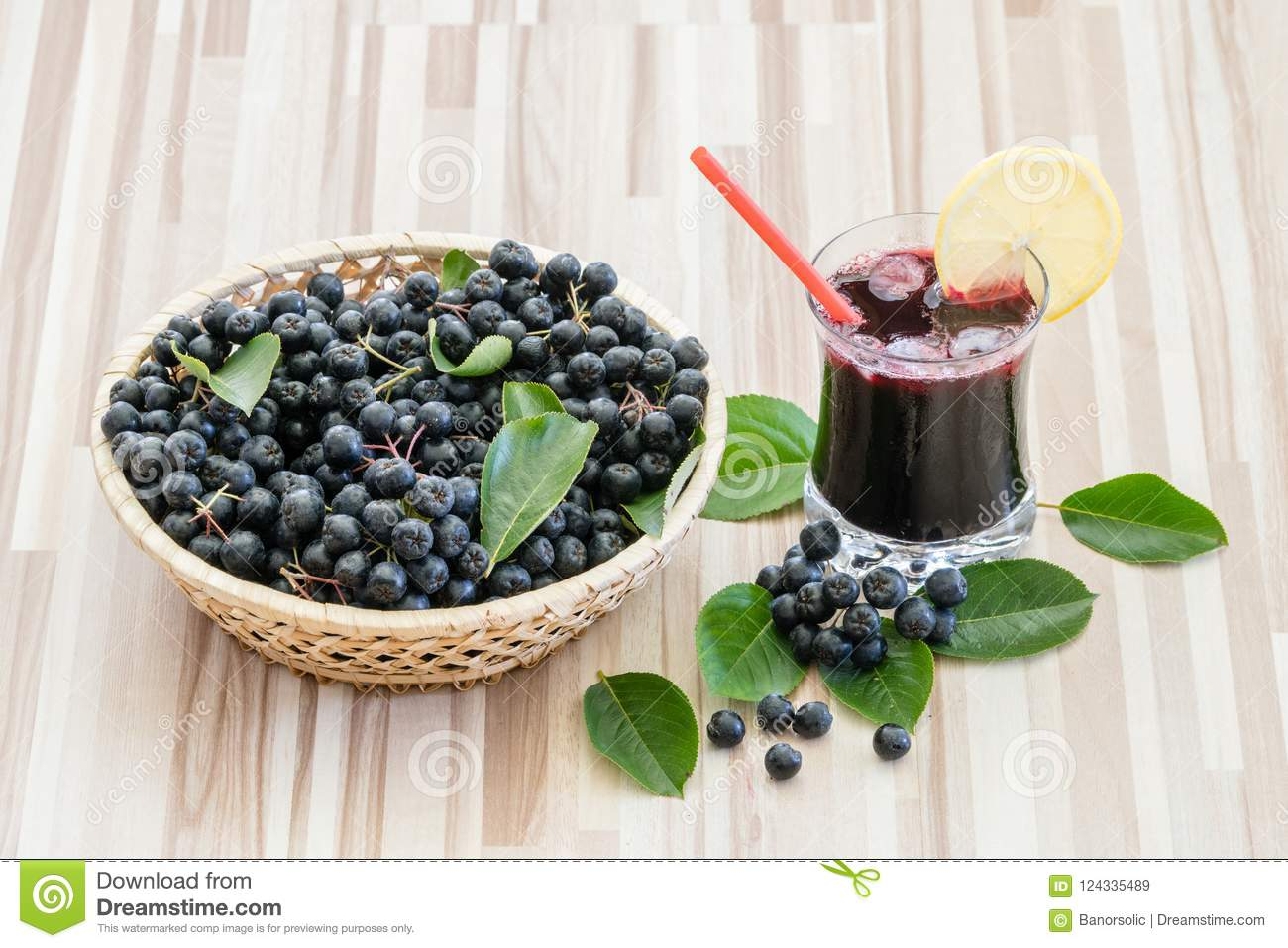 Fresh juice of chokeberry or Aronia melanocarpa in glass with ice, lemon and straw.