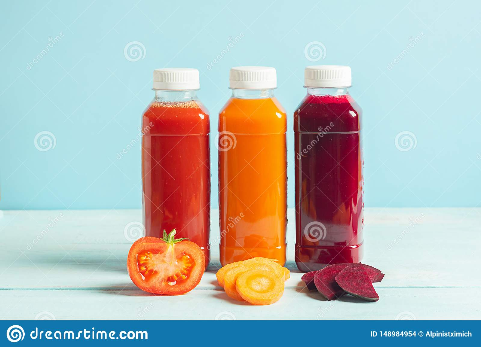 Fresh juice smoothies from a variety of vegetables carrots apple tomatoes beets in bottles on a wooden blue background