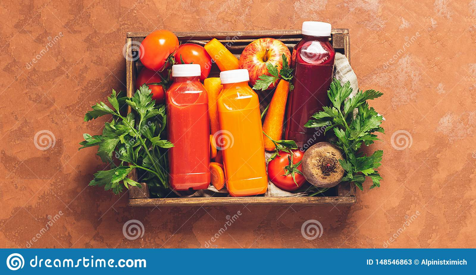 Fresh juice smoothies from a variety of vegetables carrots apple tomatoes beets bottles in wooden box brown background