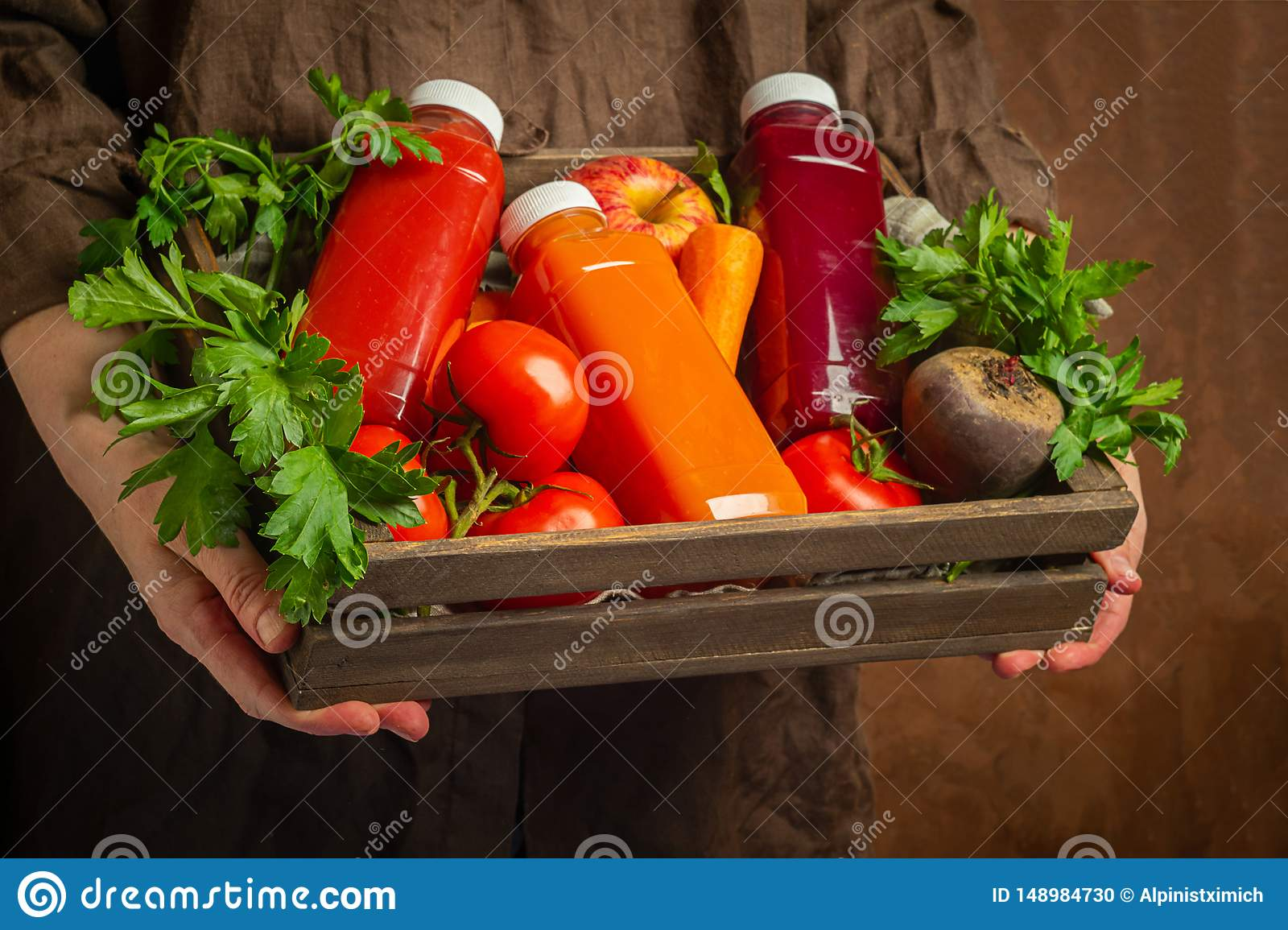Fresh juice smoothies from various vegetables carrot apple beet tomatoes in bottles in a wooden box in female hands