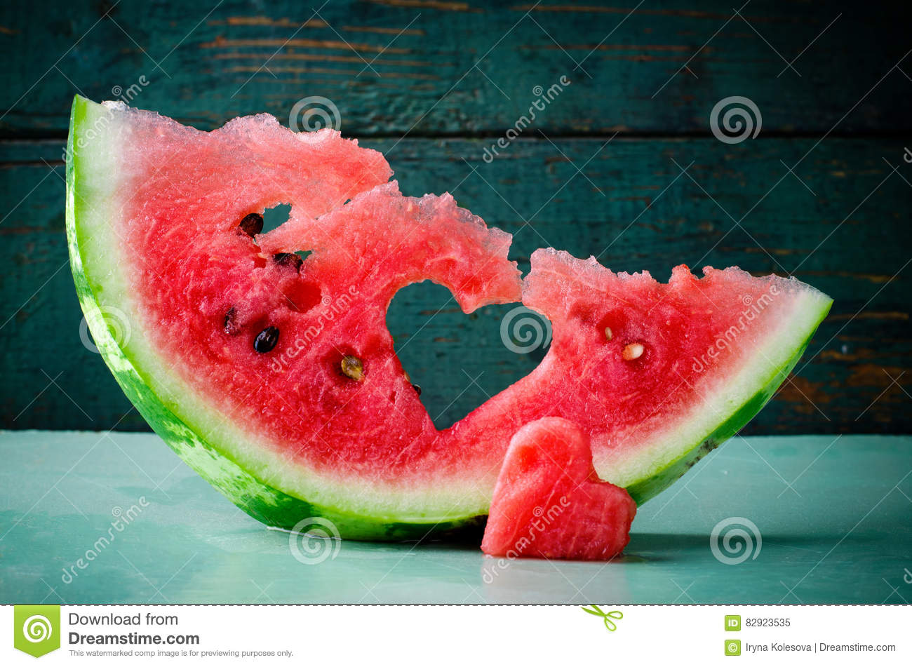 Fresh juicy watermelon heart at turquoise wooden background. Saint Valentine, love greeting card