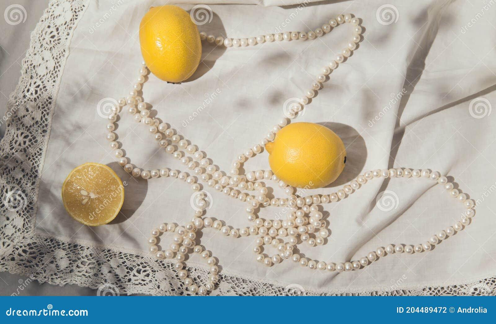Fresh Lemons With Pearl Necklace On White Fabric Background With Shades Beautiful Backdrop Stock Photo Image Of Fabric Fashion 204489472