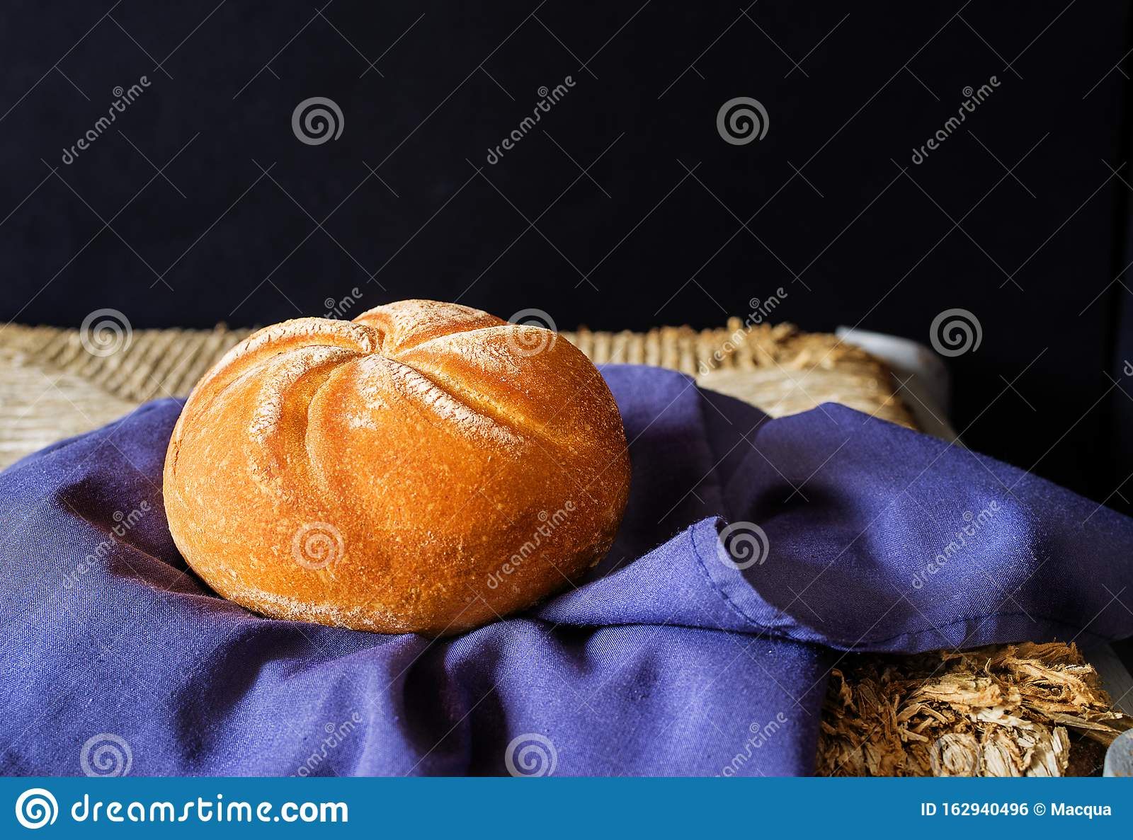 Fresh loaf on rustic stand holded in a blue napkin