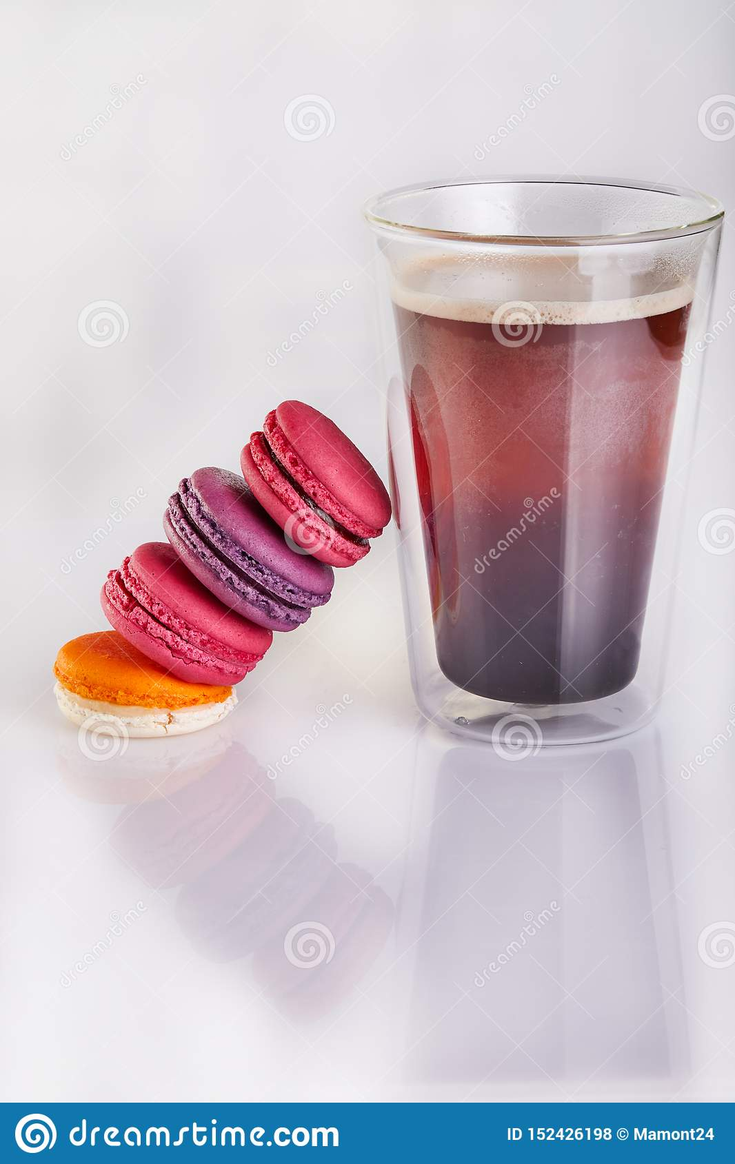 Fresh macarons of different colors and flavors and a glass of espresso coffee on a white background