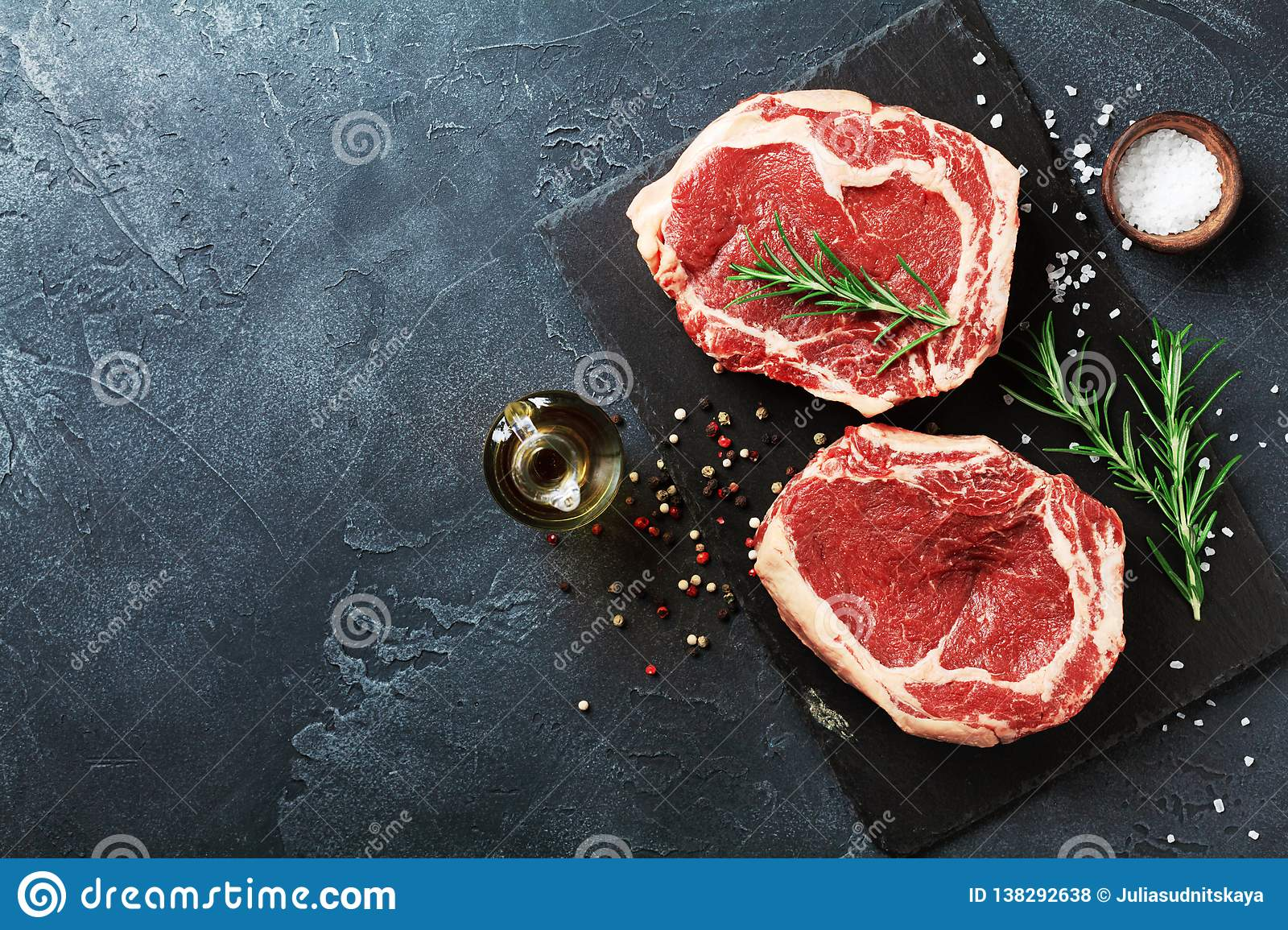 Fresh meat on slate black board top view. Raw beef steak and spices for cooking