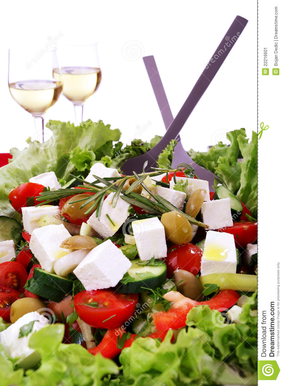 Fresh mediteranian salad with two glasses of wine