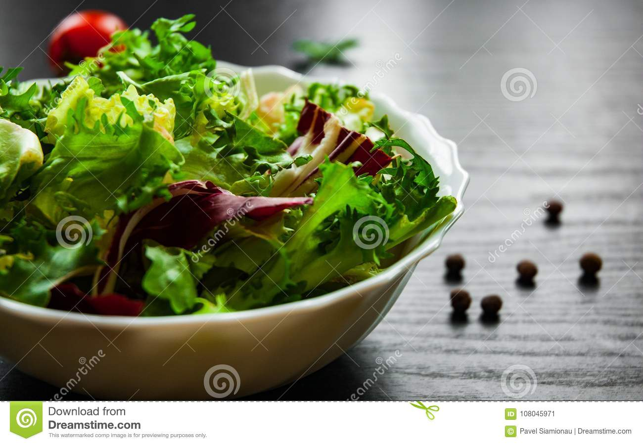 Fresh mix salad leaves with lettuce, radicchio, and rocket in bowl on dark wooden background