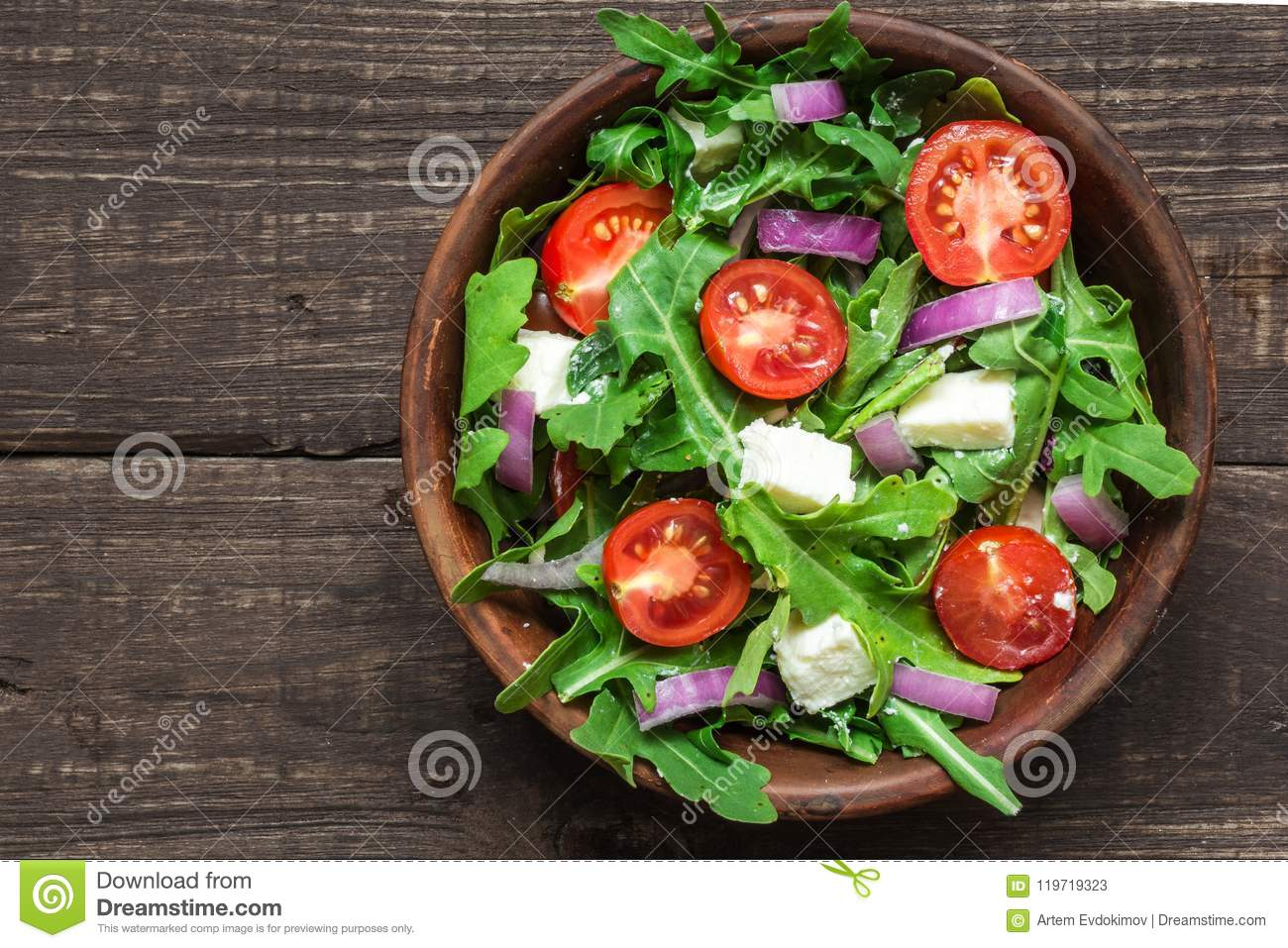 Fresh mixd salad with rucola, tomatoes cherry, feta cheese and red onion in a bowl on rustic wooden table. top view