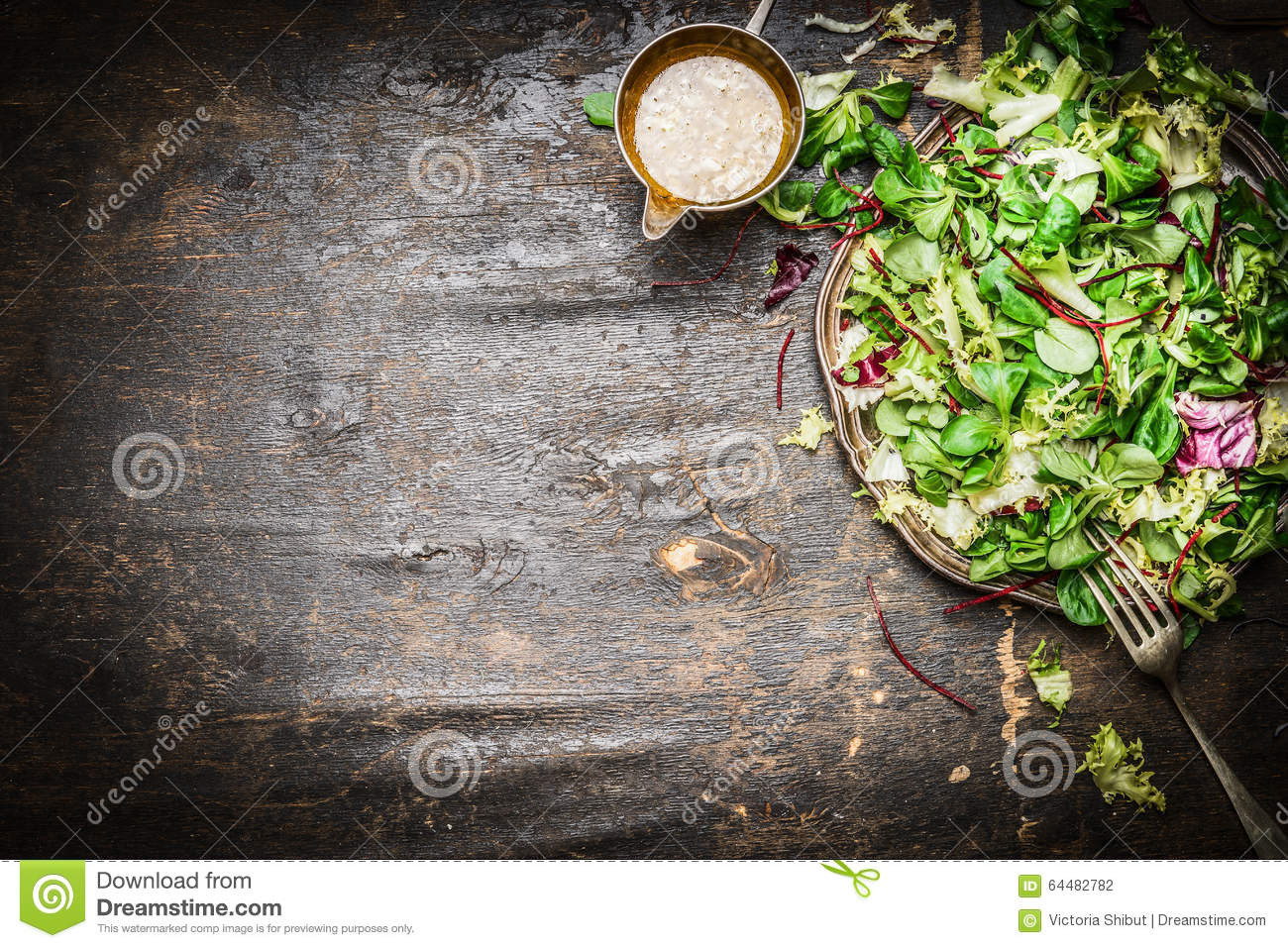 Fresh mixed green salad with oil dressing rustic wooden background, top view. Healthy food