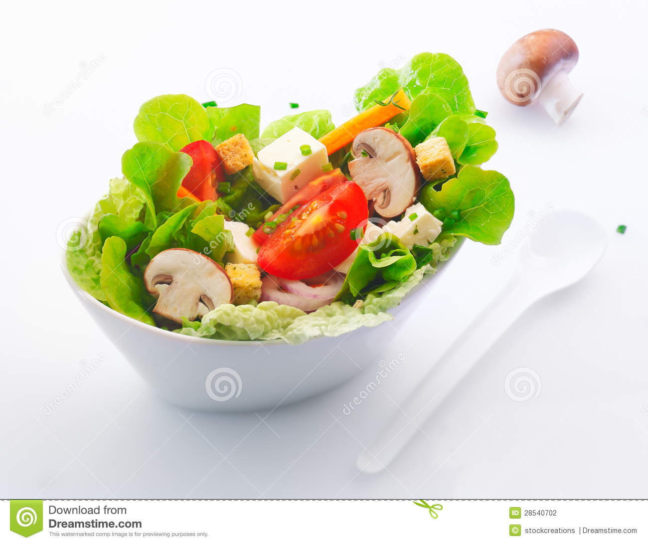 in a white china dish of fresh mixed green salad with sliced fresh ...
