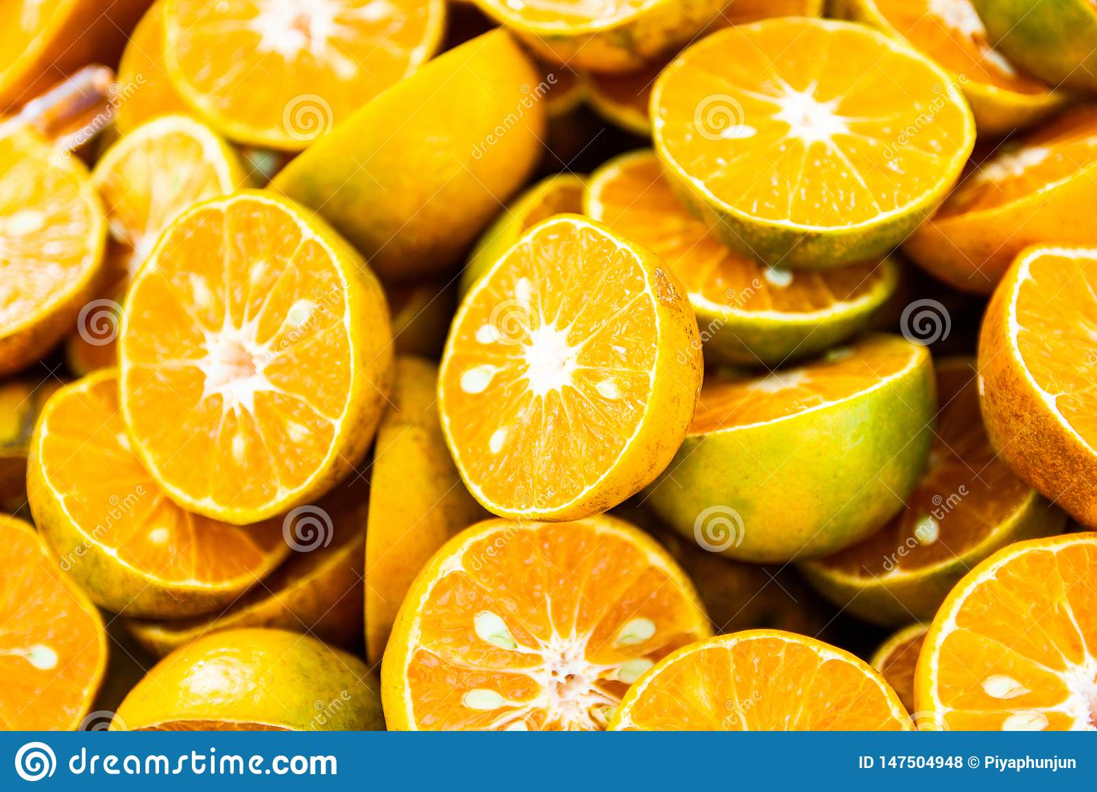 Fresh orange with orange halves on ice