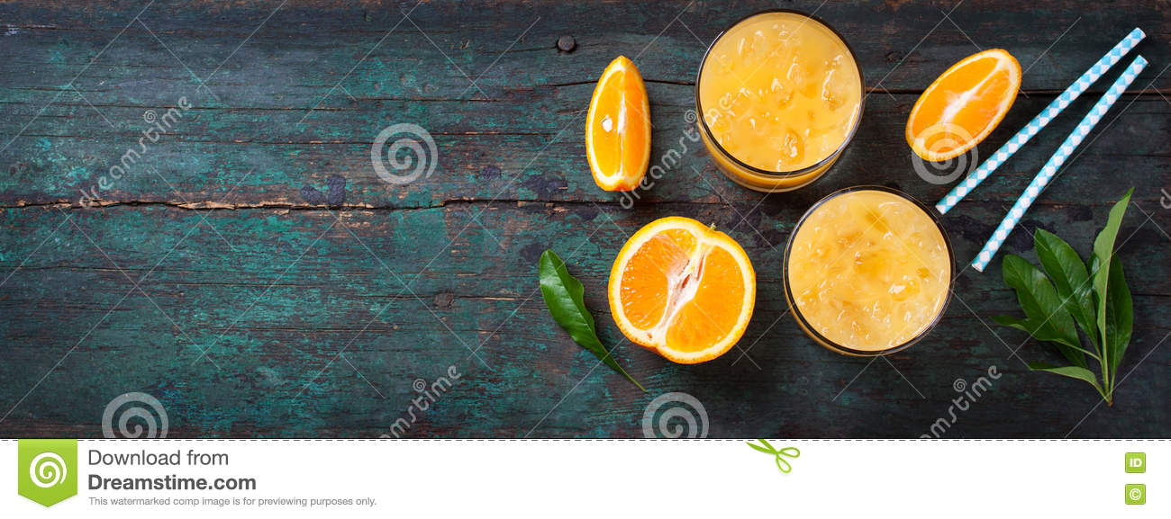 Fresh orange juice with crushed ice and fresh oranges and blue straws on an old vintage exotic background