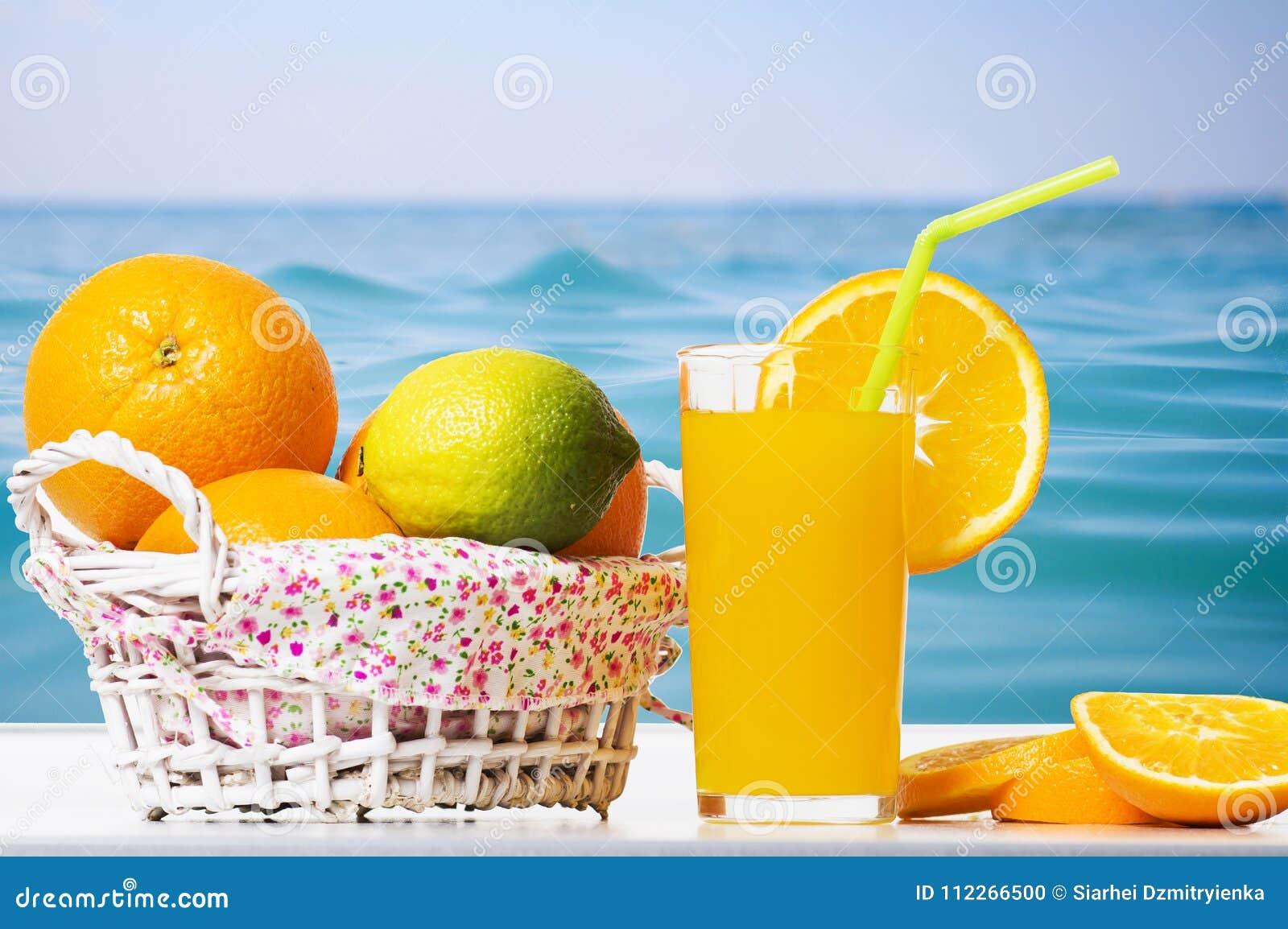 Fresh orange juice, orange slices and oranges in basket against background of surface blue sea. Summer tropical citrus fruits