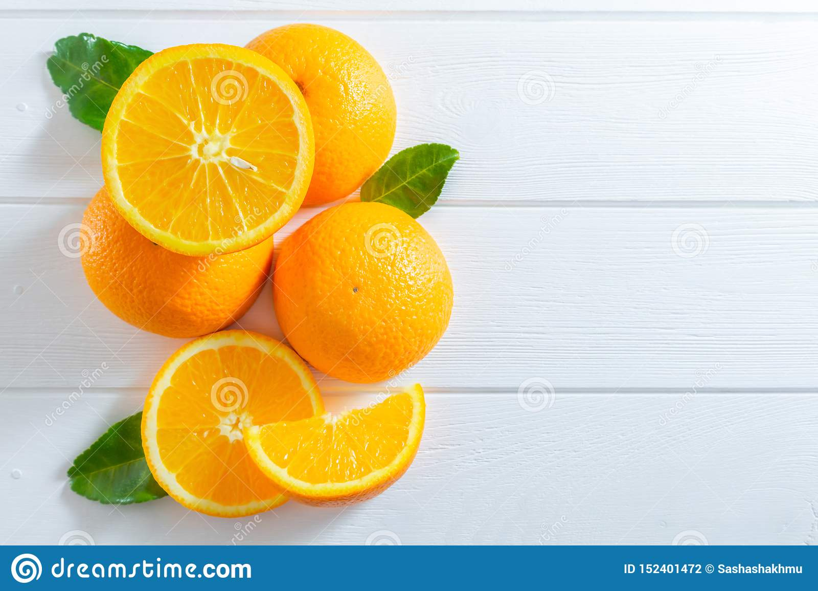 Fresh oranges and green leaves on white wooden table. Flat-lay, top view