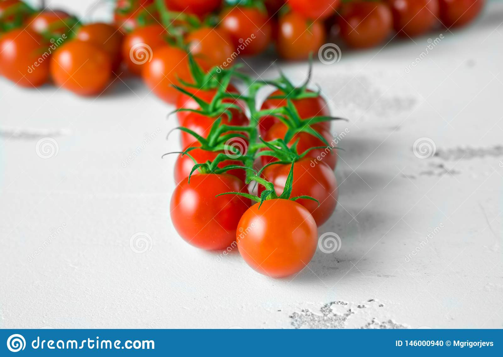 Fresh organic cherry tomatoes on white table