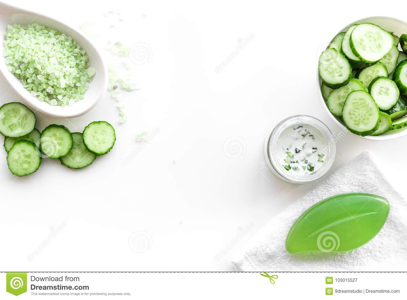 Fresh organic cosmetics with cucumber. Cream, lotion, spa salt on white background top view copyspace