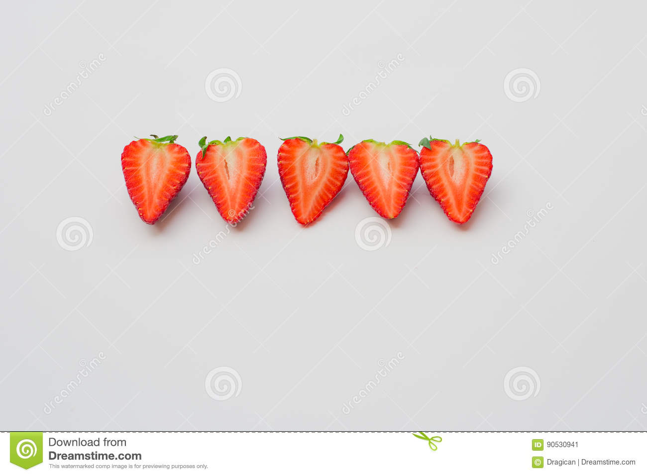 Fresh organic strawberries halved and arranged in a line on a white background.