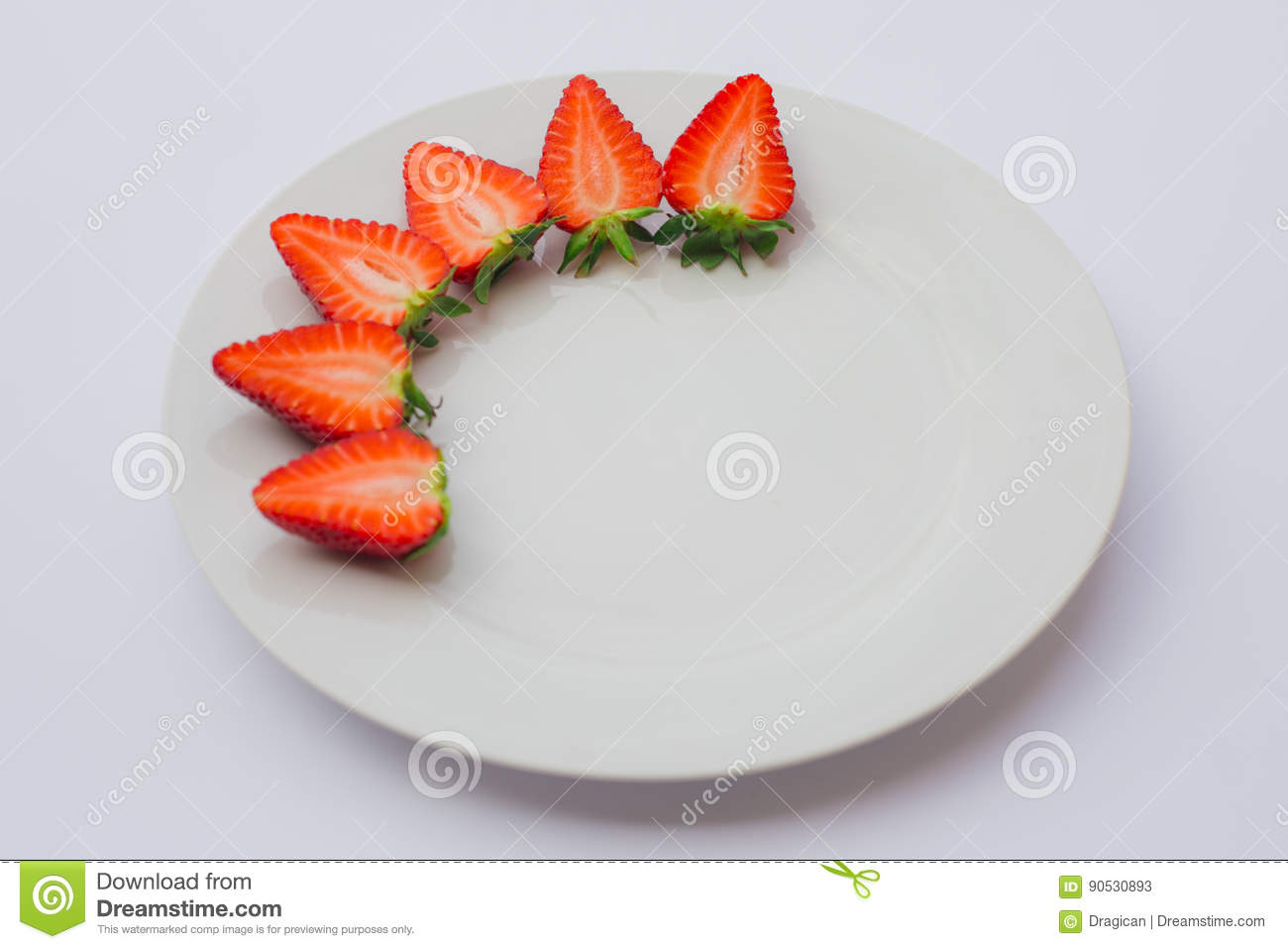 Fresh organic strawberries halved and decorated on a white plate.