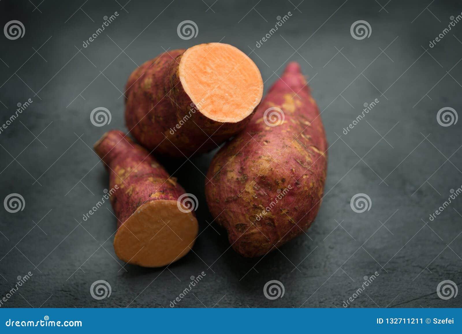Fresh organic sweet potato on dark background