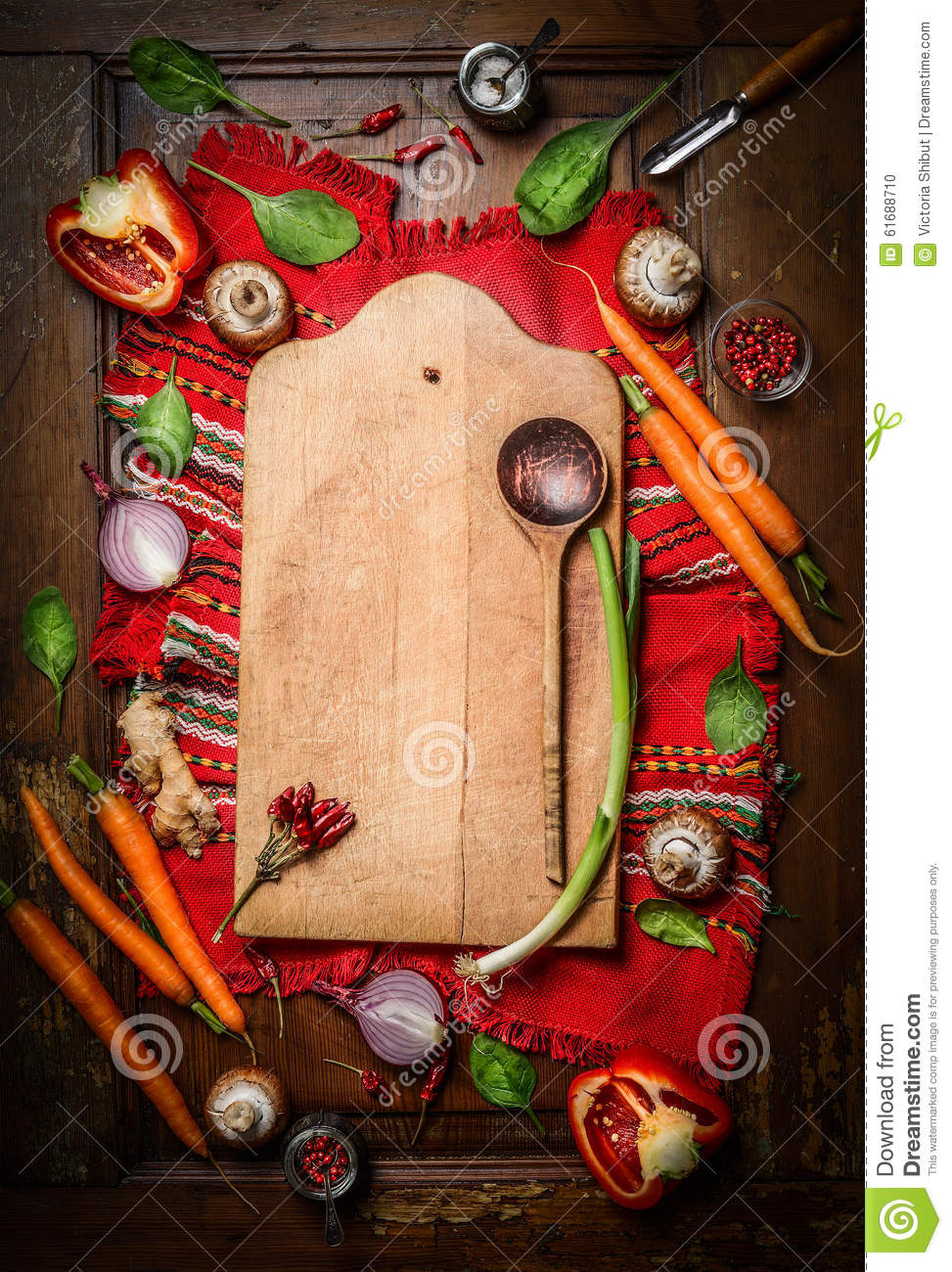 Fresh organic vegetables around old cutting board with wooden spoon on rustic napkin and wooden background. Top view, frame.