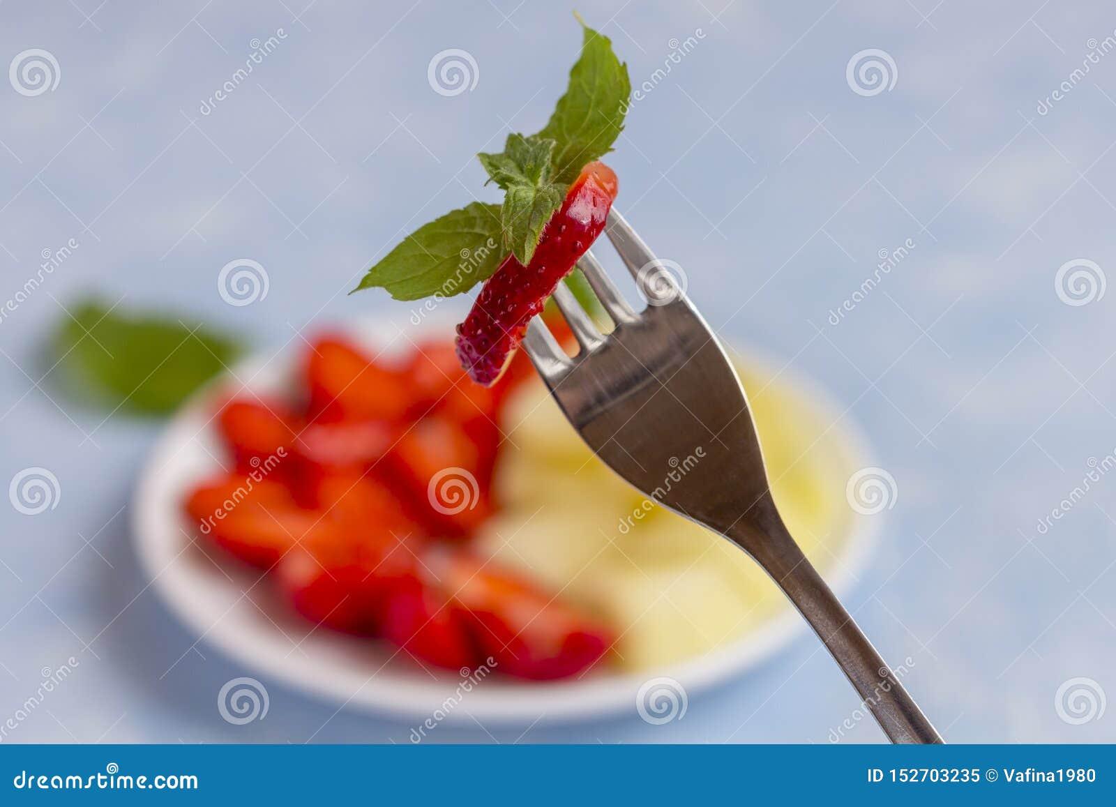Berry on a fork close up. Fresh Organic Vegetarian Fruit Salad
