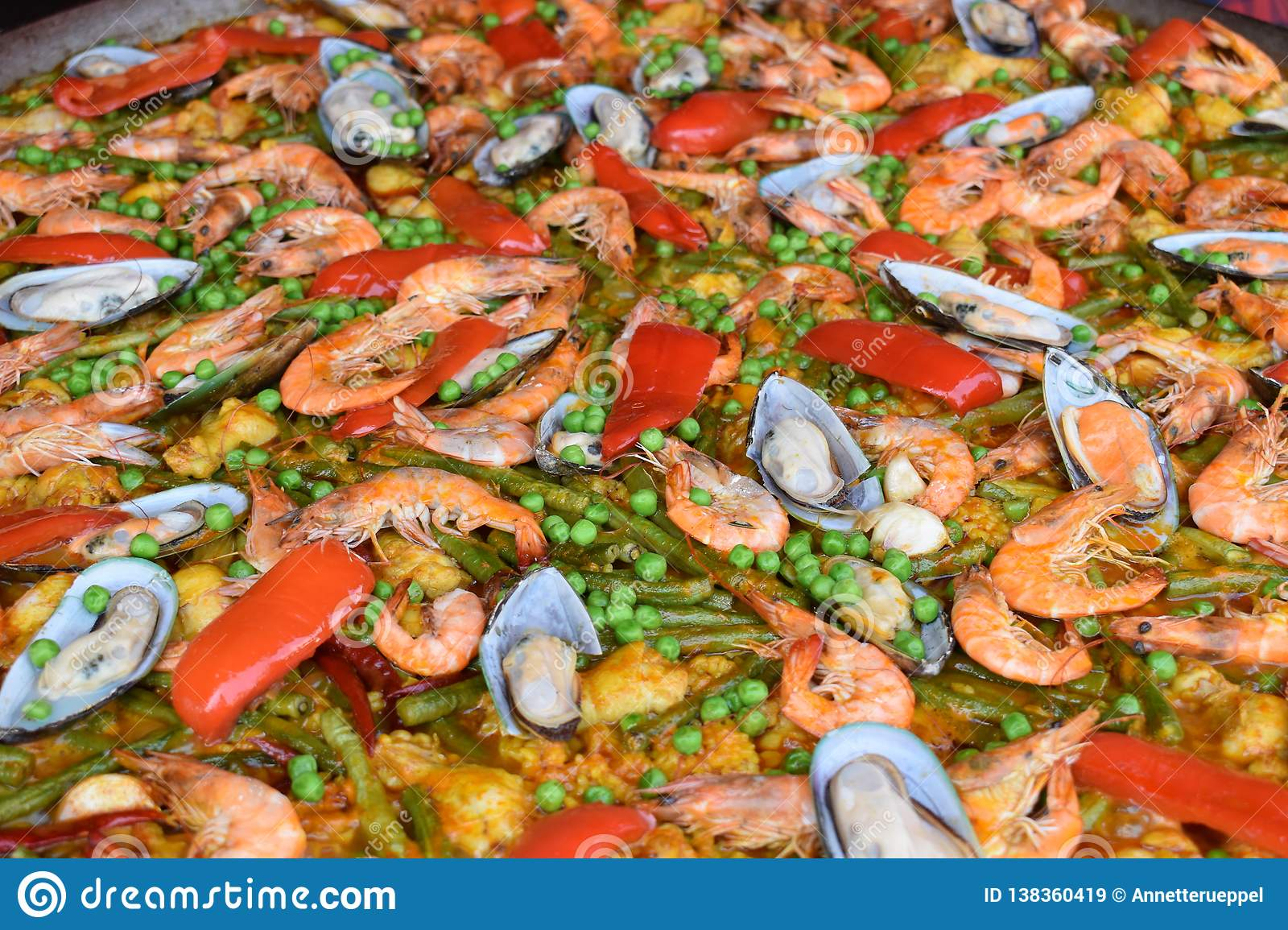 Fresh paella – a rice dish with vegetables and fresh seafood- on a food market