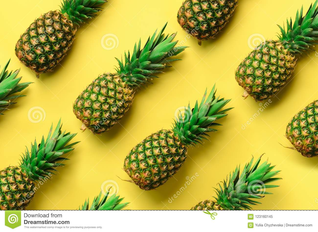 Fresh pineapples on yellow background. Top View. Pop art design, creative concept. Copy Space. Bright pineapple pattern