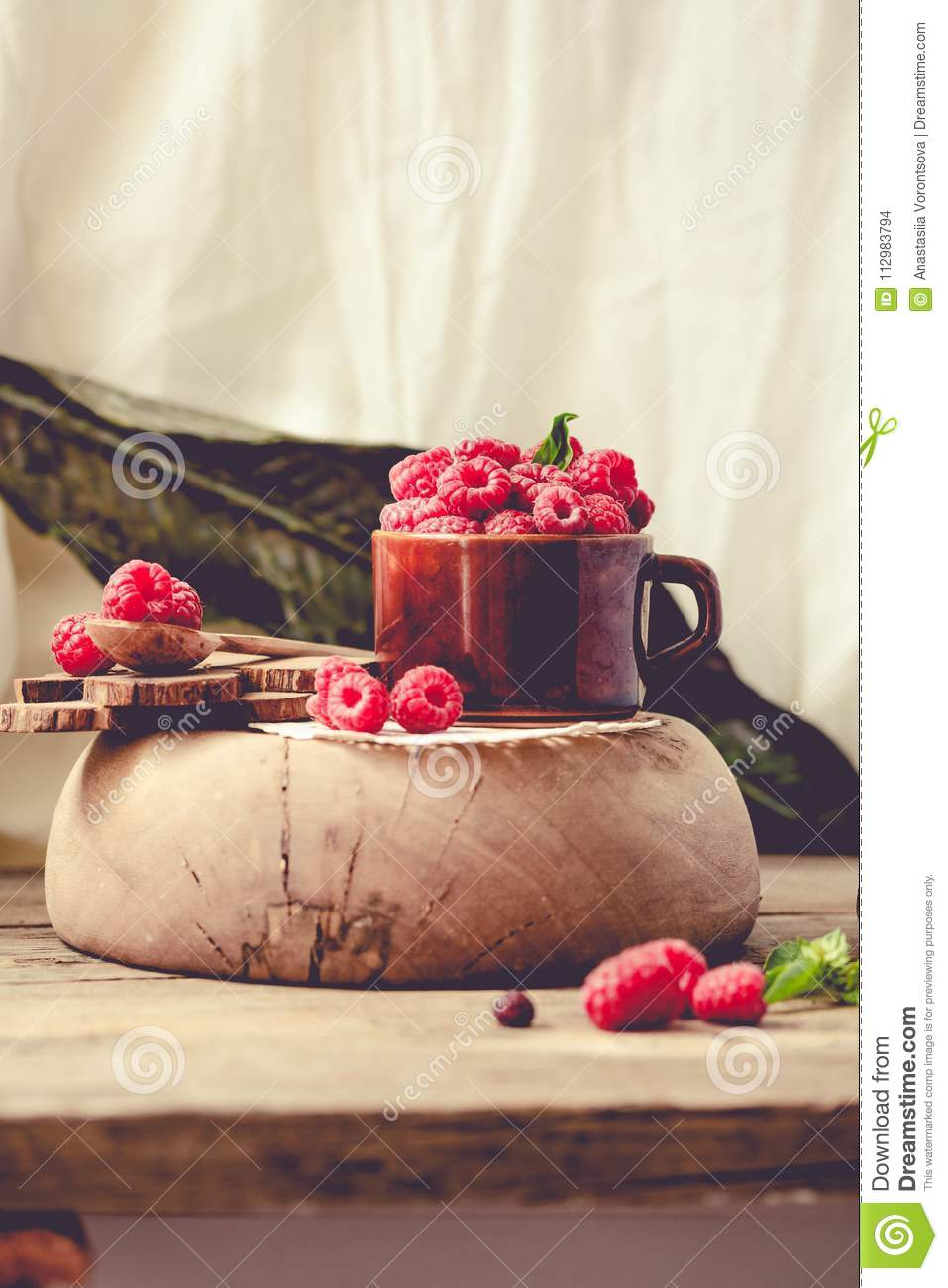 Fresh raspberry with basil in a cup of coffee and a wooden stand