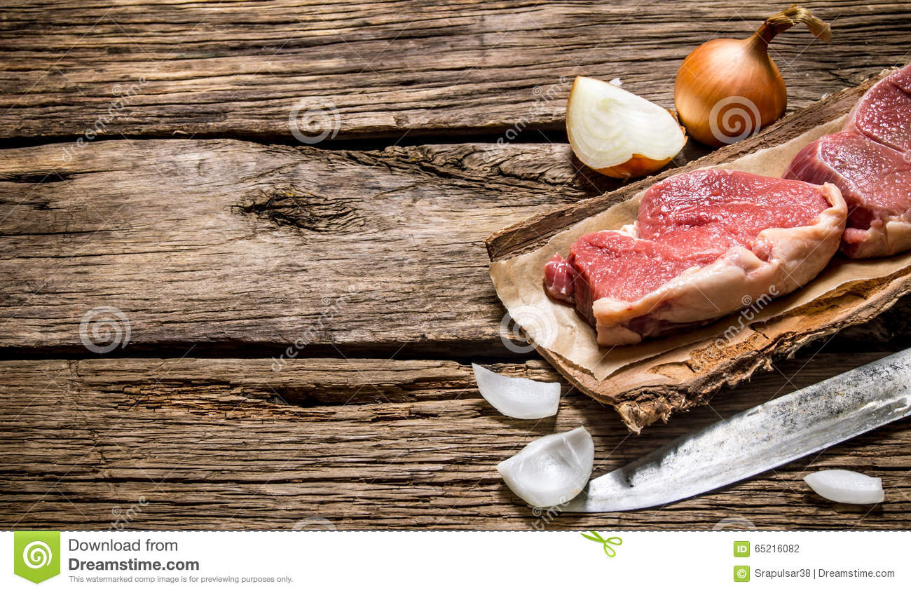 Fresh raw meat with a butcher knife and a onion.