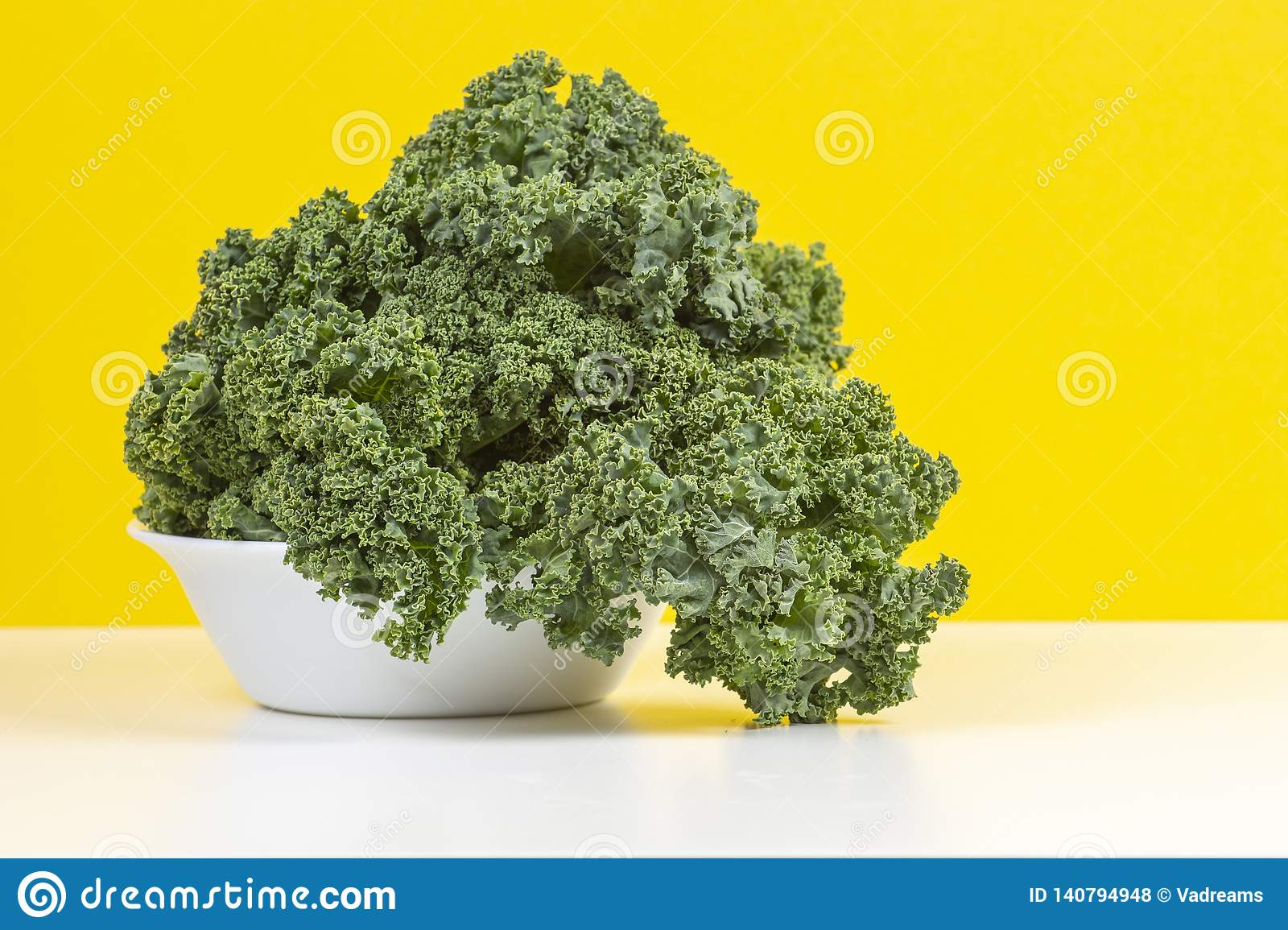 Fresh raw organic green curly kale leaves of kale on white plate with yellow background