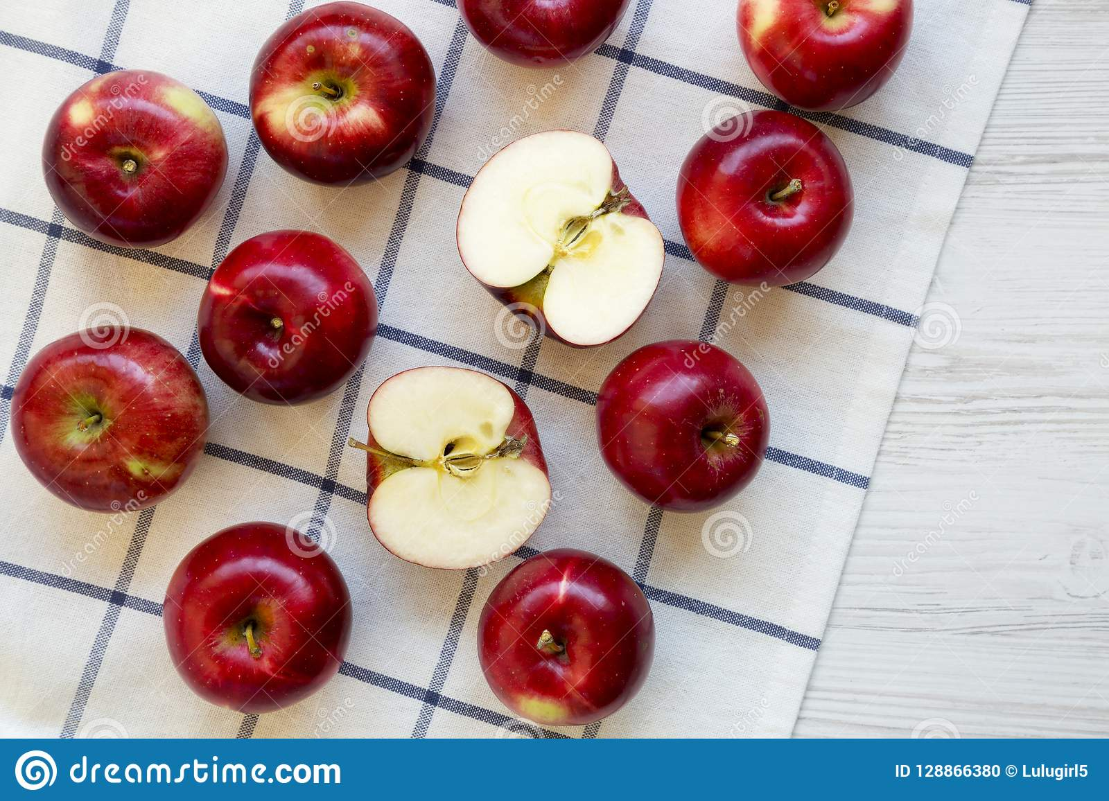 Fresh raw organic red apples on cloth over white wooden background, top view. Flat lay, from above, overhead