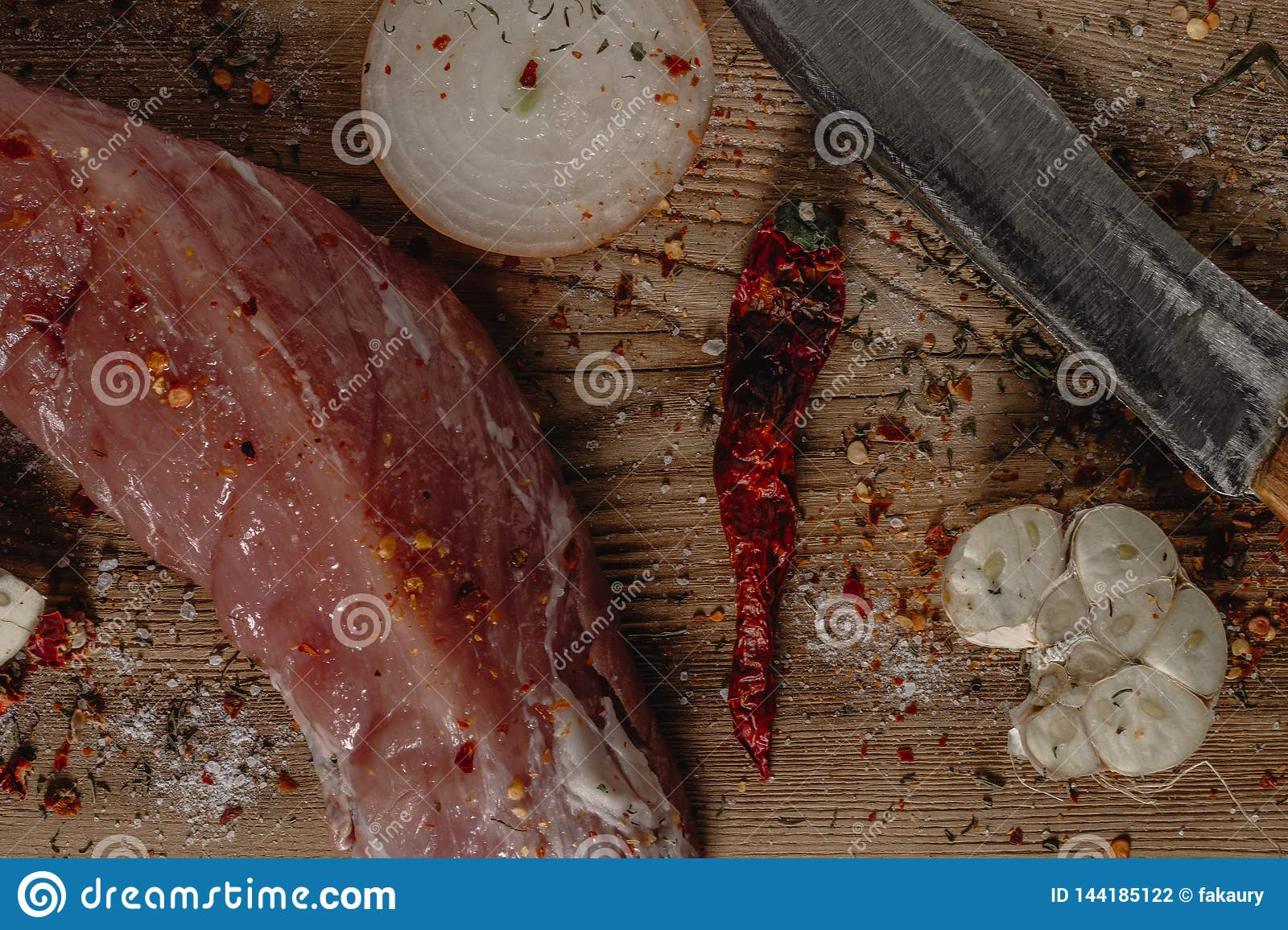 Fresh raw pork tenderloin on wooden cutting board with onion, garlic and knife