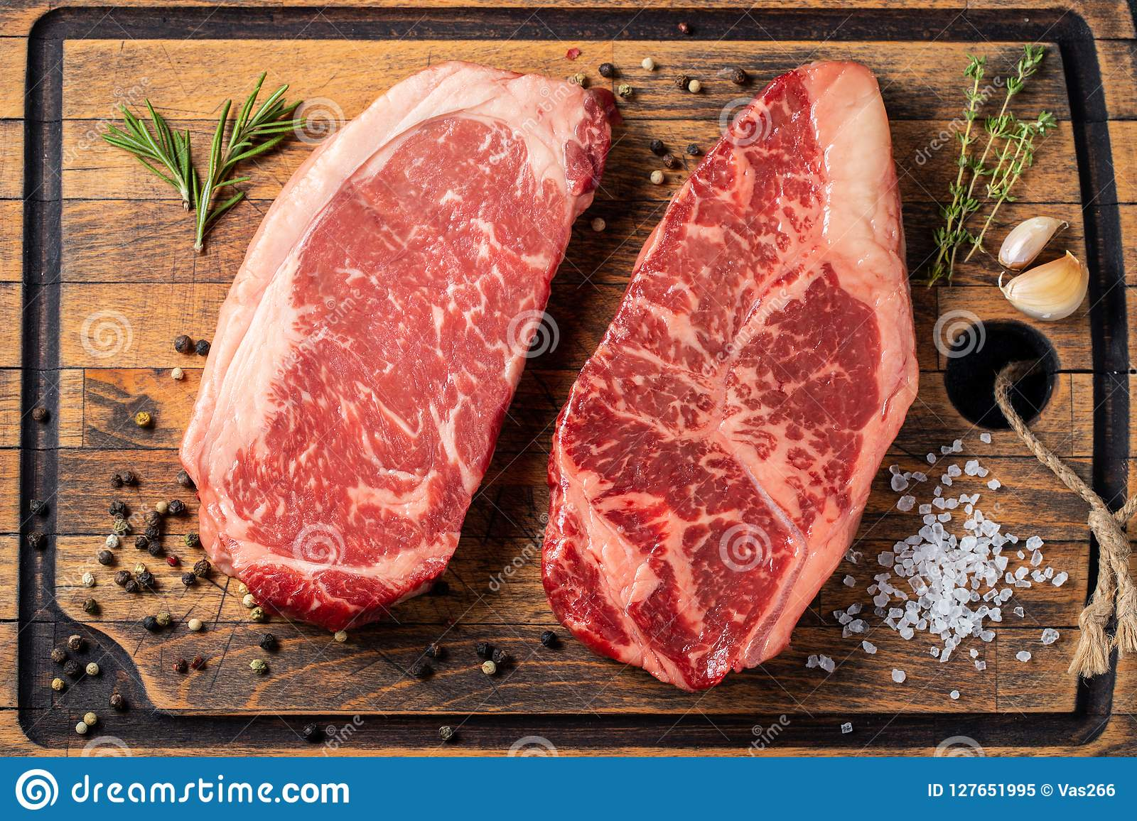 Fresh raw Prime Black Angus beef steaks with spices on wooden board: Striploin, Rib Eye. Top view. On a dark background
